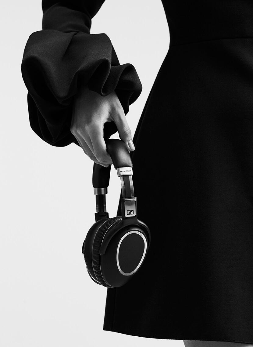 Woman holding Sennheiser headphones