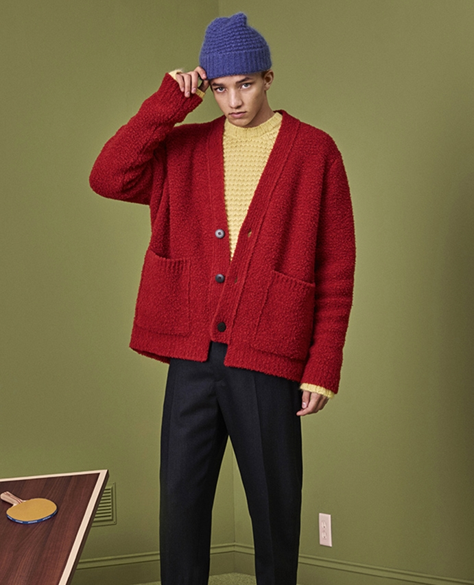 A man wearing a beanie hat, yellow sweater and red cardigan