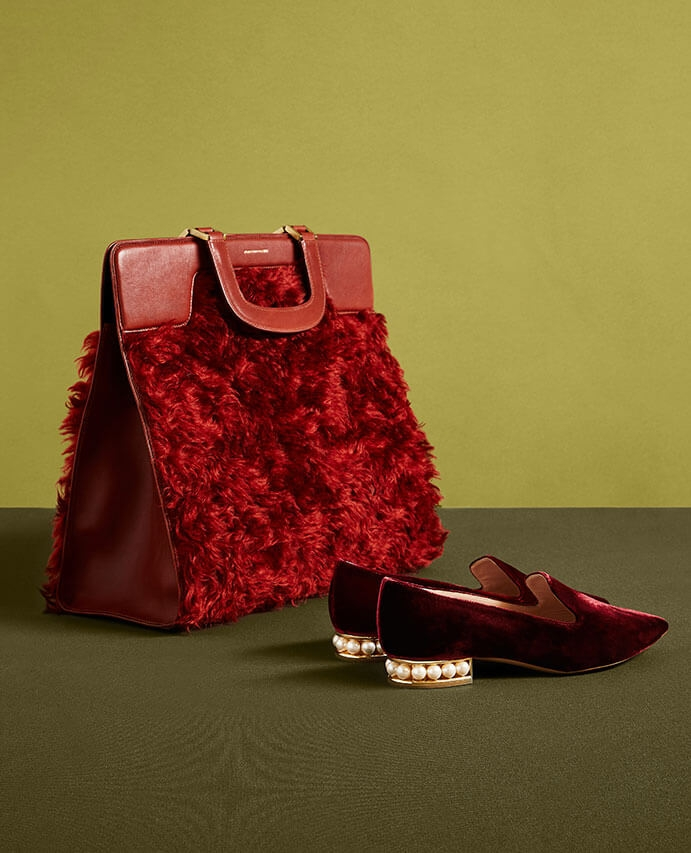 A red shearling bag and red velvet shoes