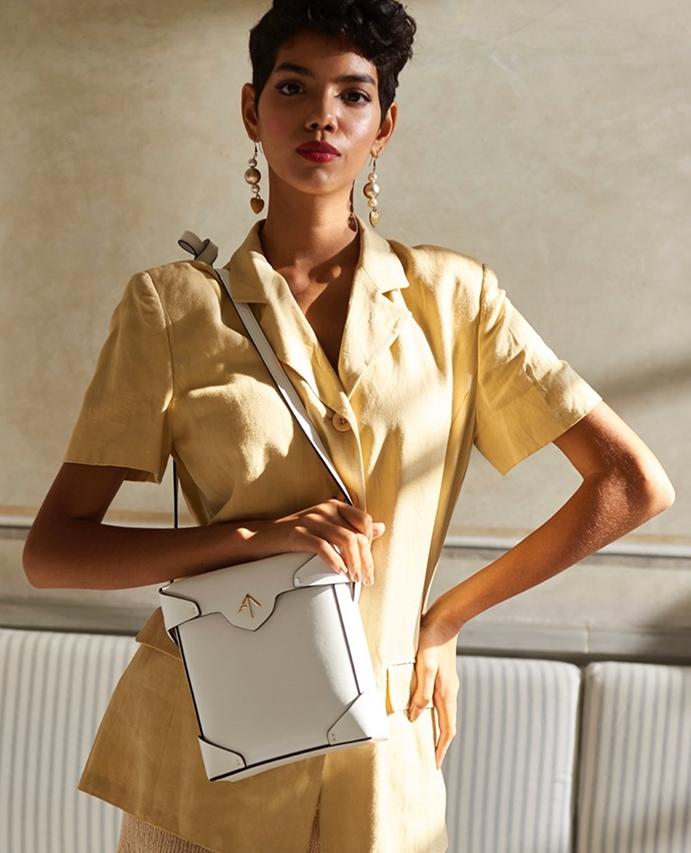 女士身穿连身裤,搭配白色 Manu Atelier 包袋