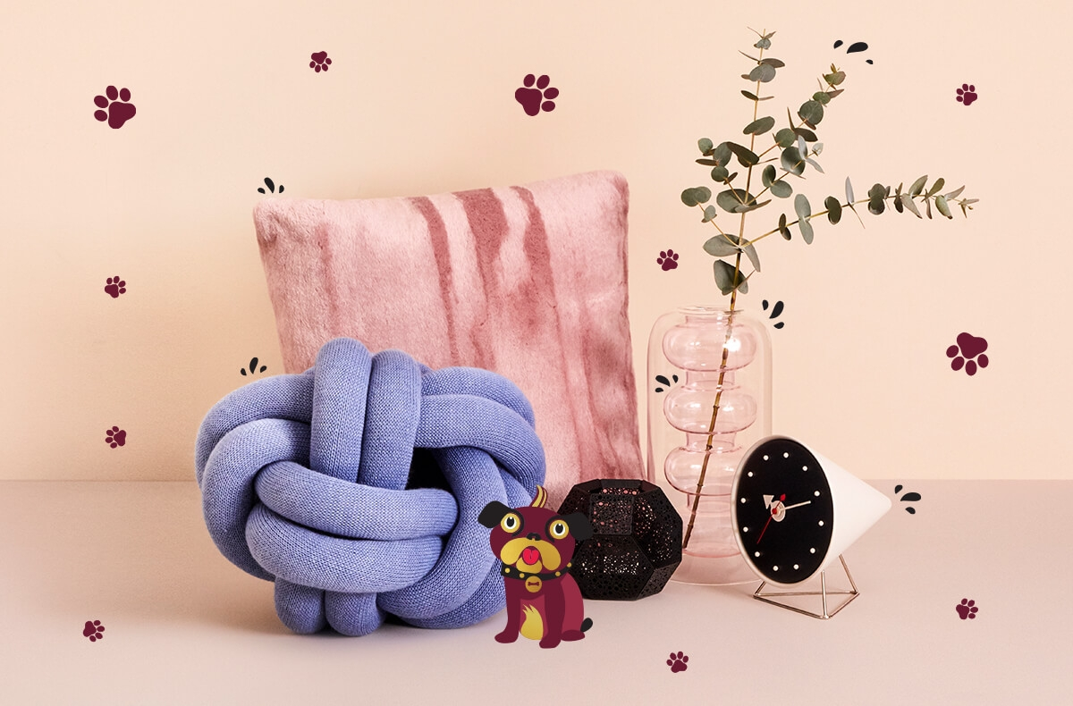 A collection of homeware products including a pink Tom Dixon cushion, vase and tea light holder