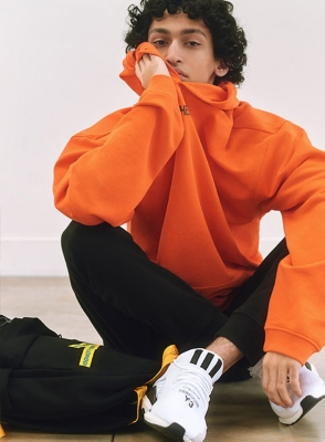 A man sitting down in an orange hoody and jogging bottoms
