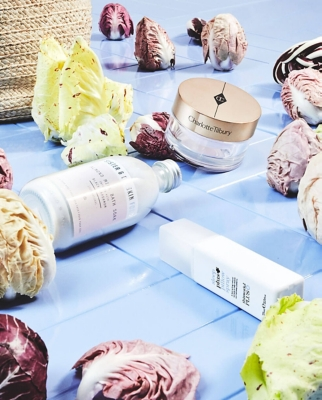 A collection of beauty products lying with cabbages