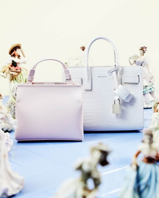 Two mini bags sitting with a collection of porcelain dolls