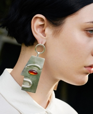 Model wears sculptural earrings