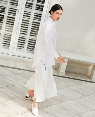 A model wearing a white shirt, skirt and shoes