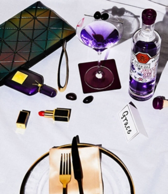 A Bao Bao Issey Miyake clutch bag with a bottle of Tom Ford Velvet orchid perfume inside next to a bottle of Zymurgorium sweet violet gin with a martini glass.