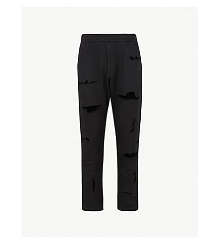 ALEXANDER MCQUEEN Distressed cotton-jersey jogging bottoms (Black