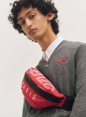 Image of a man wearing a Comme des Garcons cardigan and Kenzo bum bag