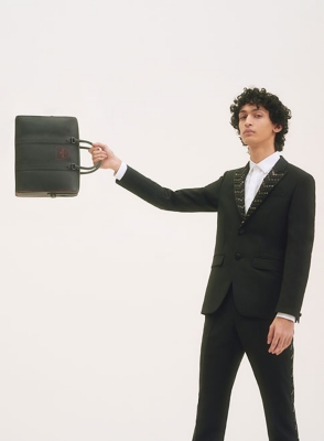 A man in a Givenchy suit and Louboutin bag
