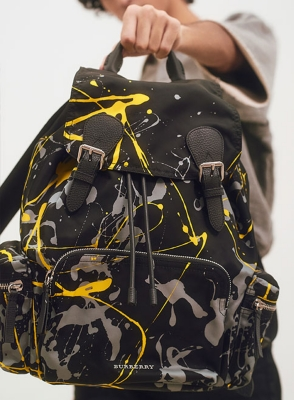 A man holding a paint-splattered Burberry backpack