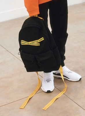 A man in track pants, white sneakers and a backpack