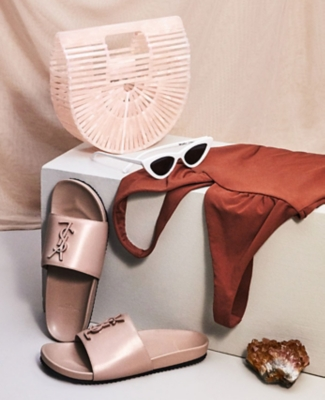 A collection of items including a Cult Gaia basket bag, YSL sandals, a swimsuit and white cateye sunglasses