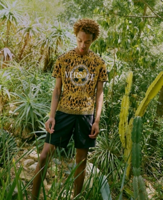 A man standing in tropical greenery in a Versace T-shirt and shorts