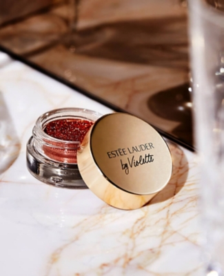 Estee Lauder red glitter pot on a table