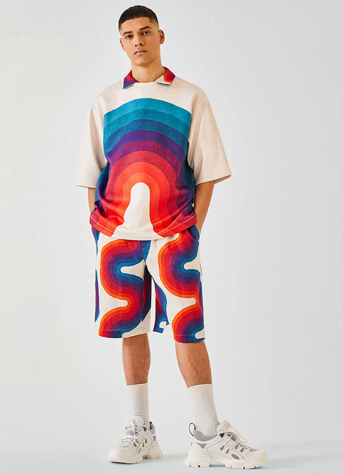 The model is wearing a Dries van Noten T-shirt, shirt and shorts with Gucci shoes