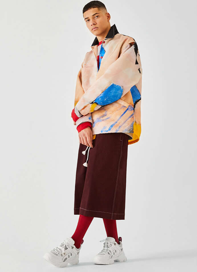 The model is wearing a Marni jacket and shorts with a pair of Gucci shoes.