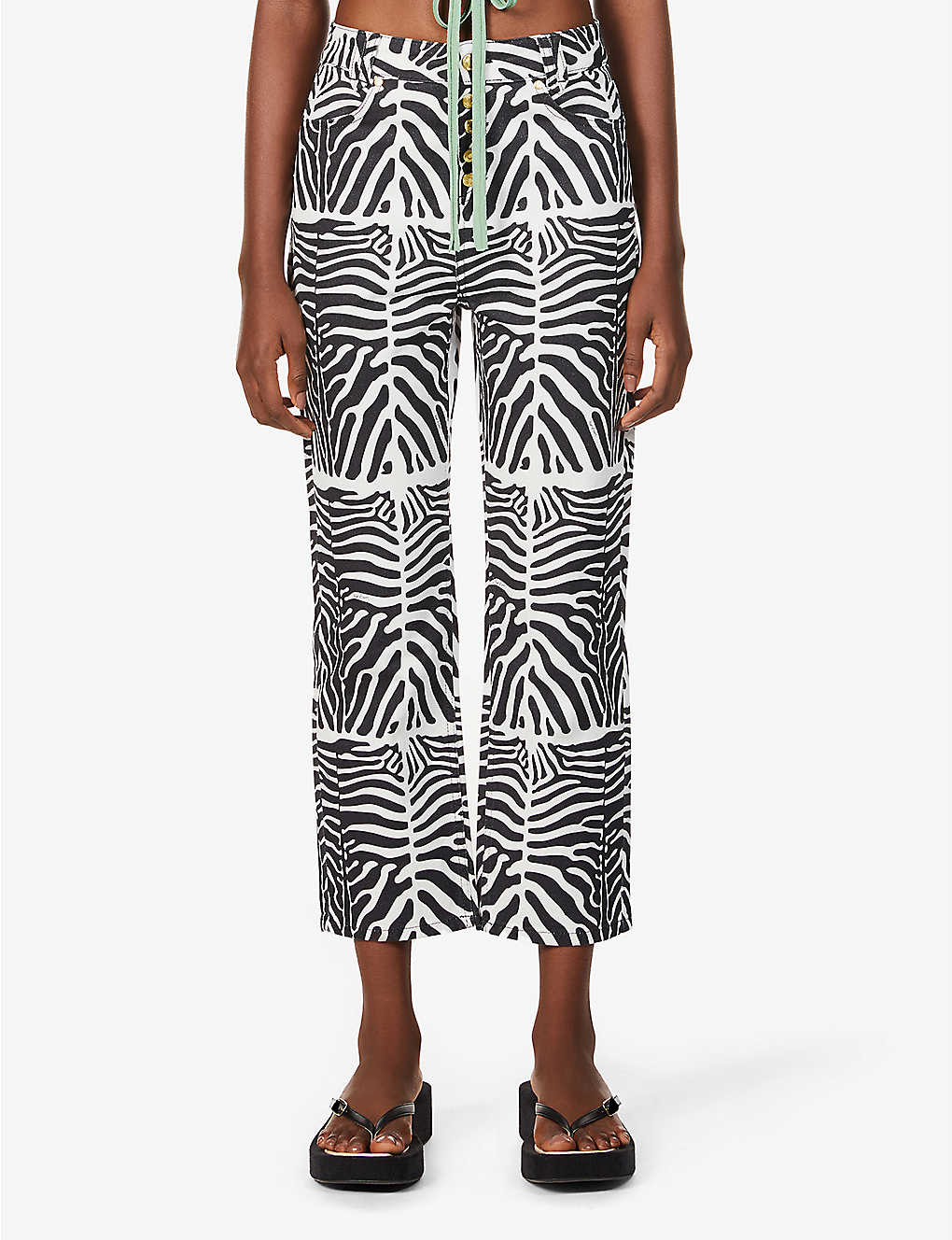Woman wears printed black and white wide-legged jeans from House of Sunny and black chunky flip flops